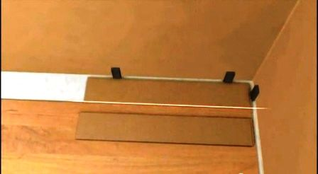 Установите клинья к стене.Планку ламината разверните лицевой стороной вниз.Сделайте отметки,проведите линию отпила,отпилите лишнее
