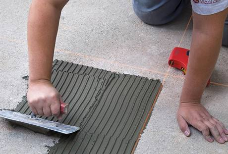нанесение плиточного клея на пол